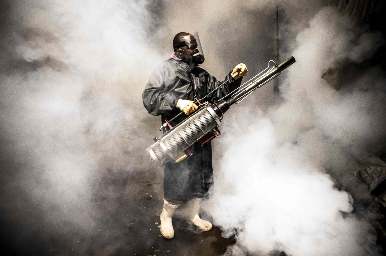 A member of a privately funded nongovernmental organization fumigates and disinfects streets and the stalls at Parklands City Park Market to help curb the spread of COVID-19, Nairobi, Kenya, April 15, 2020. (AFP Photo)