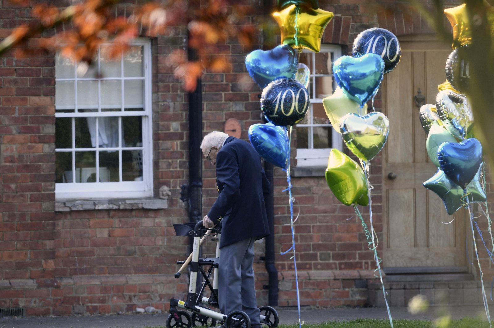 99-year old British military veteran Tom Moore, who has completed the 100th length of his garden at his home in Marston Moretaine, raising millions of pounds for the NHS with donations to his fundraising challenge from around the world, Thursday April 16, 2020. (AP Photo)
