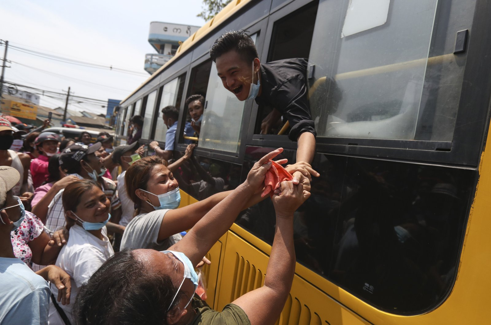 A prisoner reaches out from a bus to shake hands with family members after being released from the Insein prison during a presidential pardon in Yangon, Myanmar, Friday, April 17, 2020. (AP Photo)