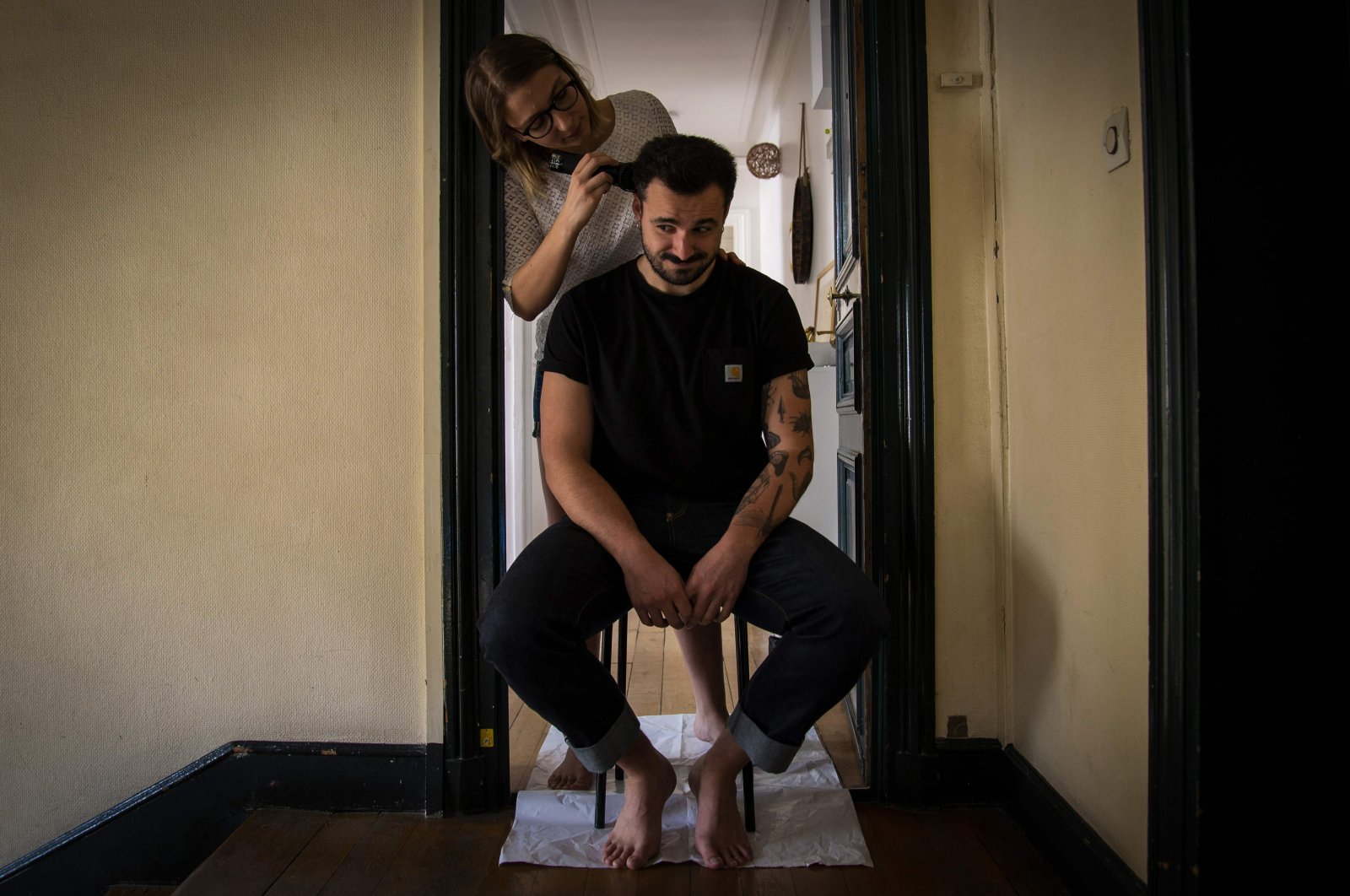 Lucie cuts her companion Pierre's hair at home as coiffeurs stay closed on the 25th day of a strict lockdown aimed at curbing the spread of COVID-19, Paris, April 10, 2020. (Photo by Elena FUSCO / AFP)
