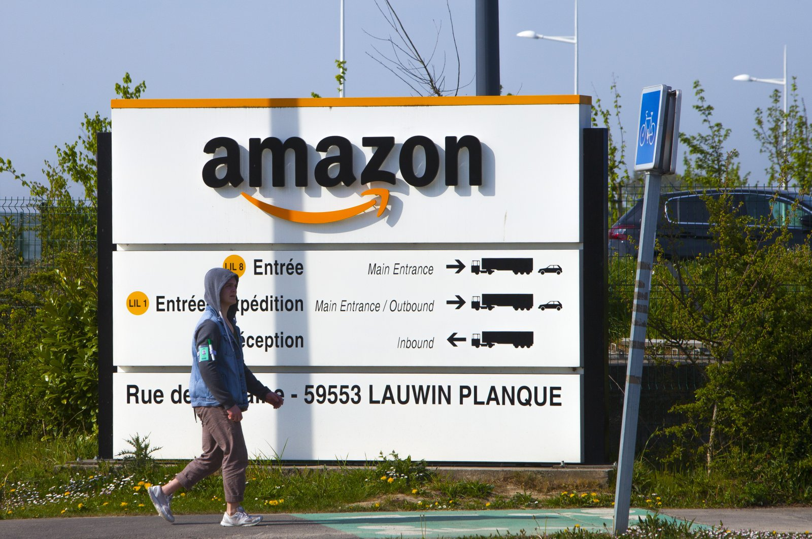 A man walks at the entrance of Amazon, in Douai, northern France, April 16, 2020. (AP Photo)