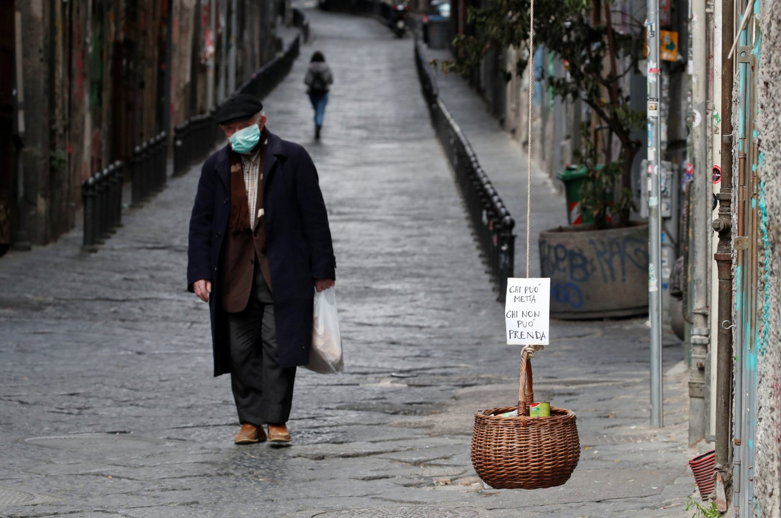 A basket hung up so people can donate or take for free food is seen, as Italy struggles to contain the spread of coronavirus disease (COVID-19), in Naples, Italy March 30, 2020.(Reuters Photo)