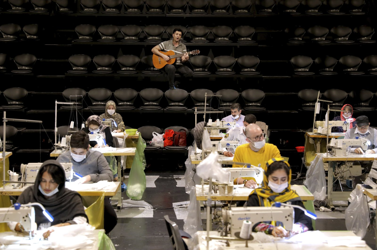 Volunteers wearing face masks to curb the spread of the new coronavirus, sew face masks, as a guitarist plays for volunteers, at the Hafez theatre hall in downtown Tehran, Iran, April 15, 2020. (AP Photo)