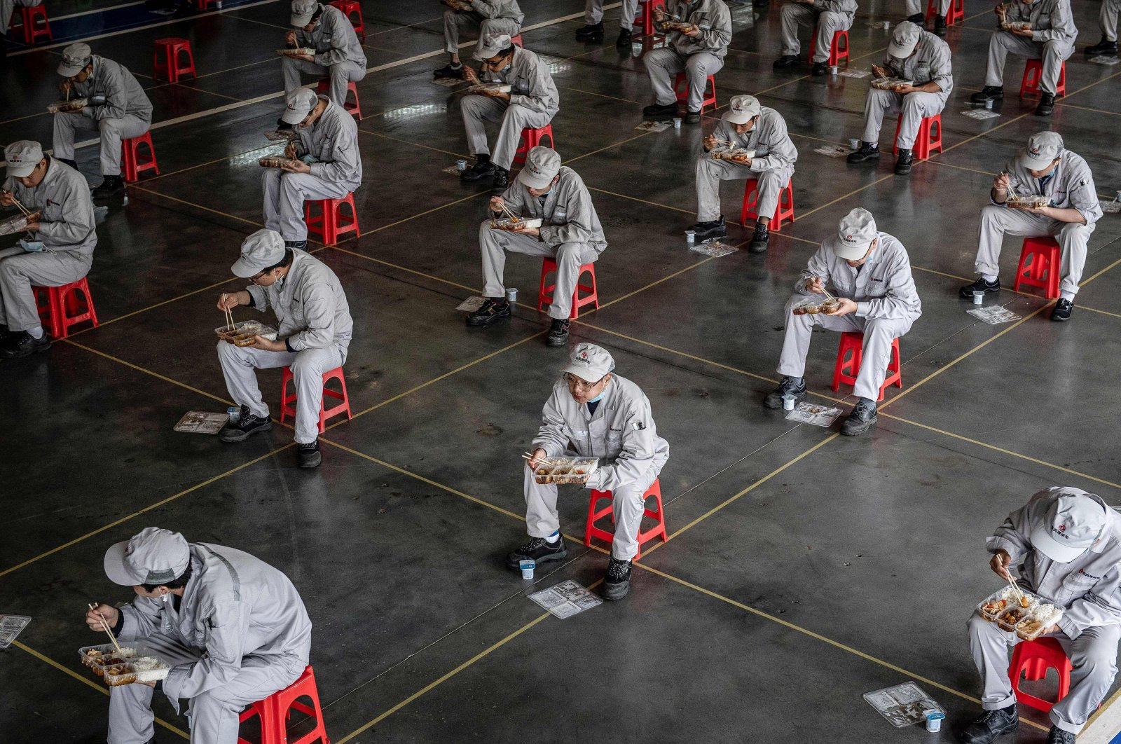 Employees eating during lunch break at an auto plant of Dongfeng Honda in Wuhan in China's central Hubei province, April 17, 2020. (AFP Photo)