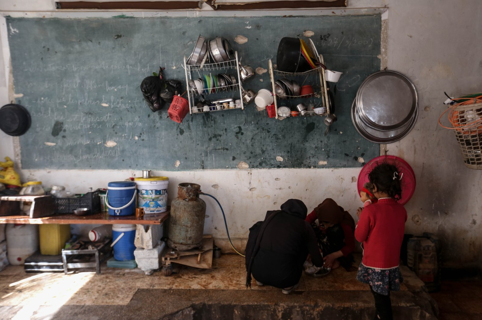 Families staying in bombed-out schools aim to transform the damaged buildings into makeshift homes by using blackboards as a place to hang clothes and turning some classrooms into kitchens, Friday, April 17, 2020. (AA)