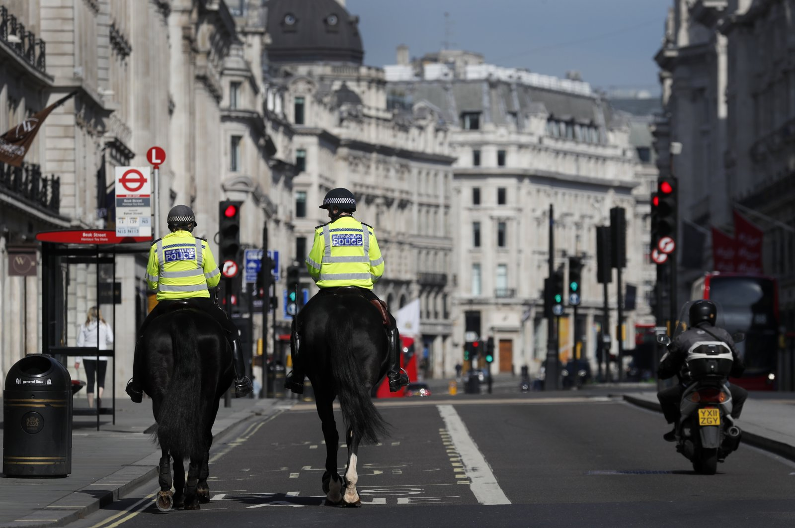 Mounted police officers patrol along a deserted Regent Street in London, as the U.K. is in lockdown to help curb the spread of the coronavirus, April 15, 2020. (AP Photo)