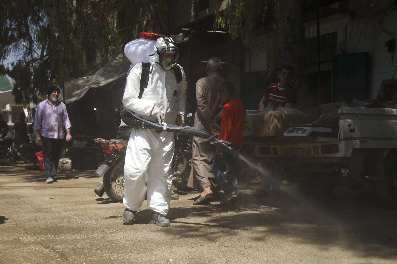 A member of a nongovernmental aid organization sprays disinfectant as a preventative measure against the coronavirus in the town of Armanaz, Idlib province, Syria, April 14, 2020. (AP Photo)
