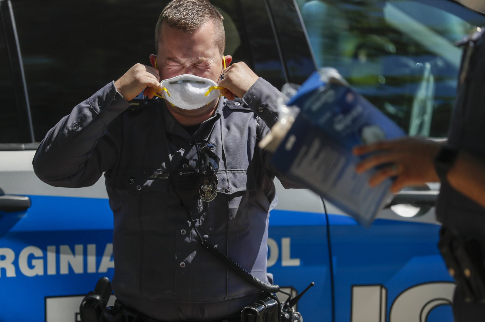 A police officer puts on a mask as protesters upset with the government's stay-at-home order due to the coronavirus pandemic rally at the State Capitol in Richmond, Virginia, U.S., April 16, 2020. (EPA Photo)