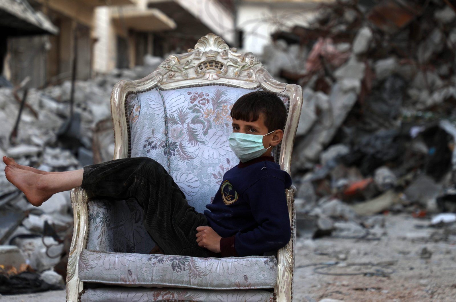 A child sits on a couch found in a street, ravaged by pro-regime forces air strikes, in the town of Ariha in the northern countryside of the Idlib province, Saturday, April 11, 2020. (AFP)