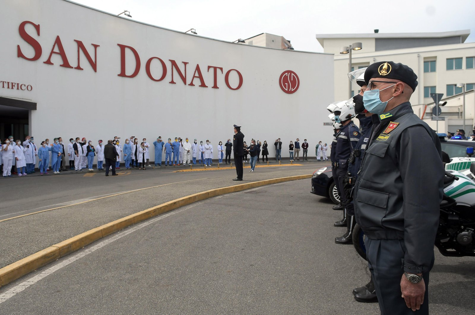 Italian law enforcement officers wearing protective face masks praise medical staff amid the ongoing coronavirus COVID-19 pandemic in front of the Polyclinic of San Donato Milanese, on the outskirts of Milan, northern Italy, April 17, 2020. (EPA Photo)