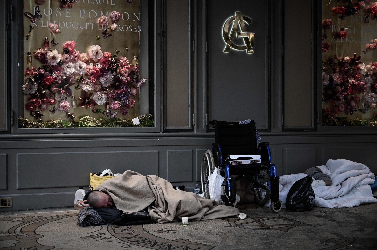 A homeless person sleeps in front of closed shops in Paris on April 17, 2020, on the 32nd day of a strict lockdown in France aimed at curbing the spread of the COVID-19 pandemic caused by the novel coronavirus. (AFP Photo)