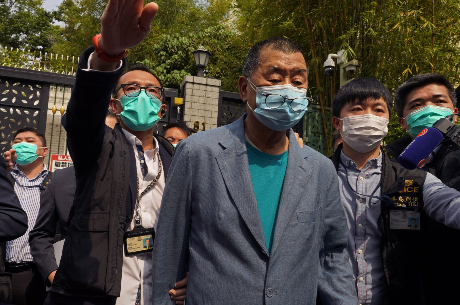 Hong Kong media tycoon Jimmy Lai, center, who founded local newspaper Apple Daily, is arrested by police officers at his home in Hong Kong, Saturday, April 18, 2020. (AP Photo)