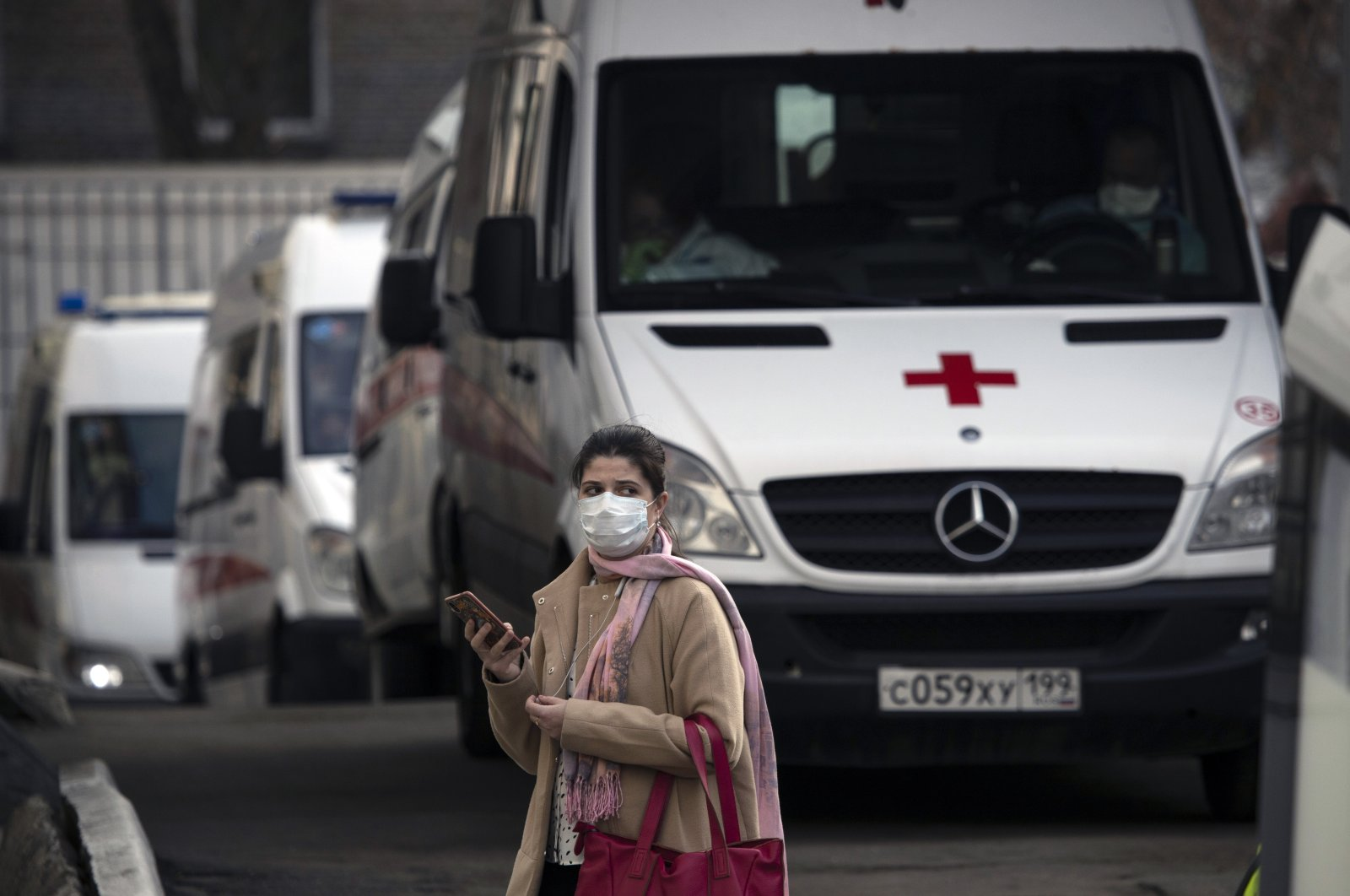 A woman wearing a face mask stands next to ambulances as they queue to transfer patients suspected of having the coronavirus infection to a hospital in Moscow, Russia, April 9, 2020. (AP Photo)