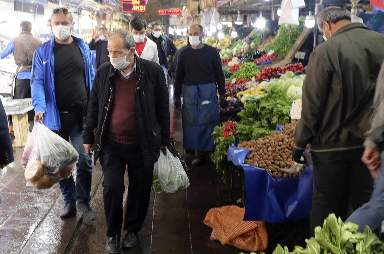 People wearing face masks leave a food market just hours before the start of a two-day curfew declared by the government in an attempt to slow down the spread of coronavirus, in Ankara, Turkey, Friday, April 17, 2020. (AP Photo)
