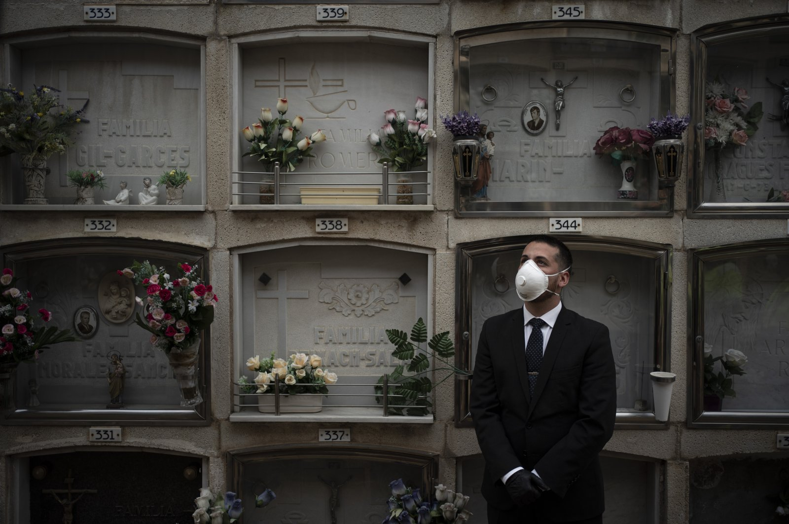 A funeral home worker wearing a face mask watches as the body of an unidentified person who died of unknown causes is placed into a niche at the Girona Cemetery in Girona, Spain, Friday, April 17, 2020. (AP Photo)