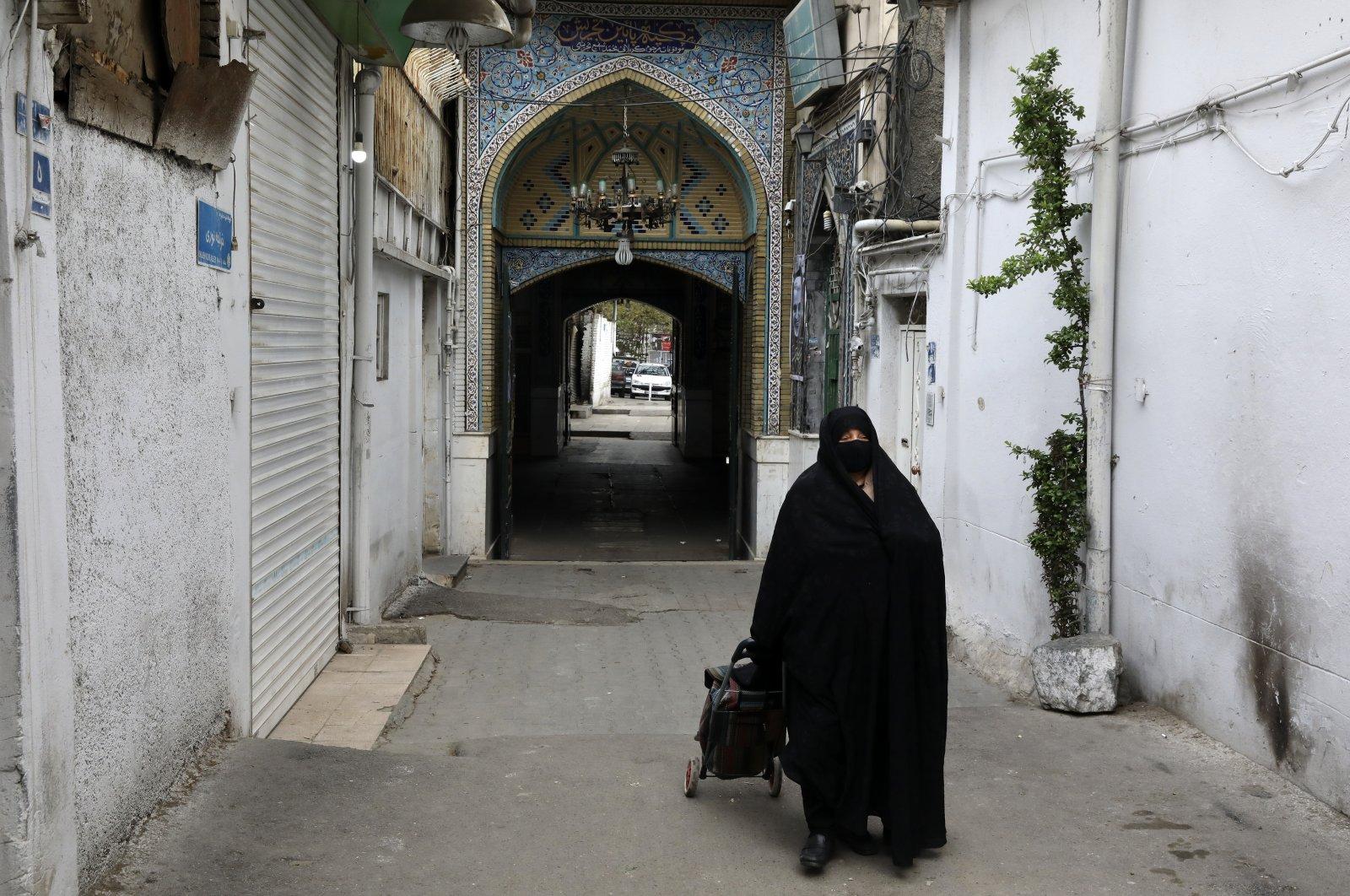 A head-to-toe veiled woman wearing a face mask to curb the spread of the new coronavirus walks in Tajrish neighborhood in northern Tehran, Iran, Thursday, April 16, 2020. (AP Photo)