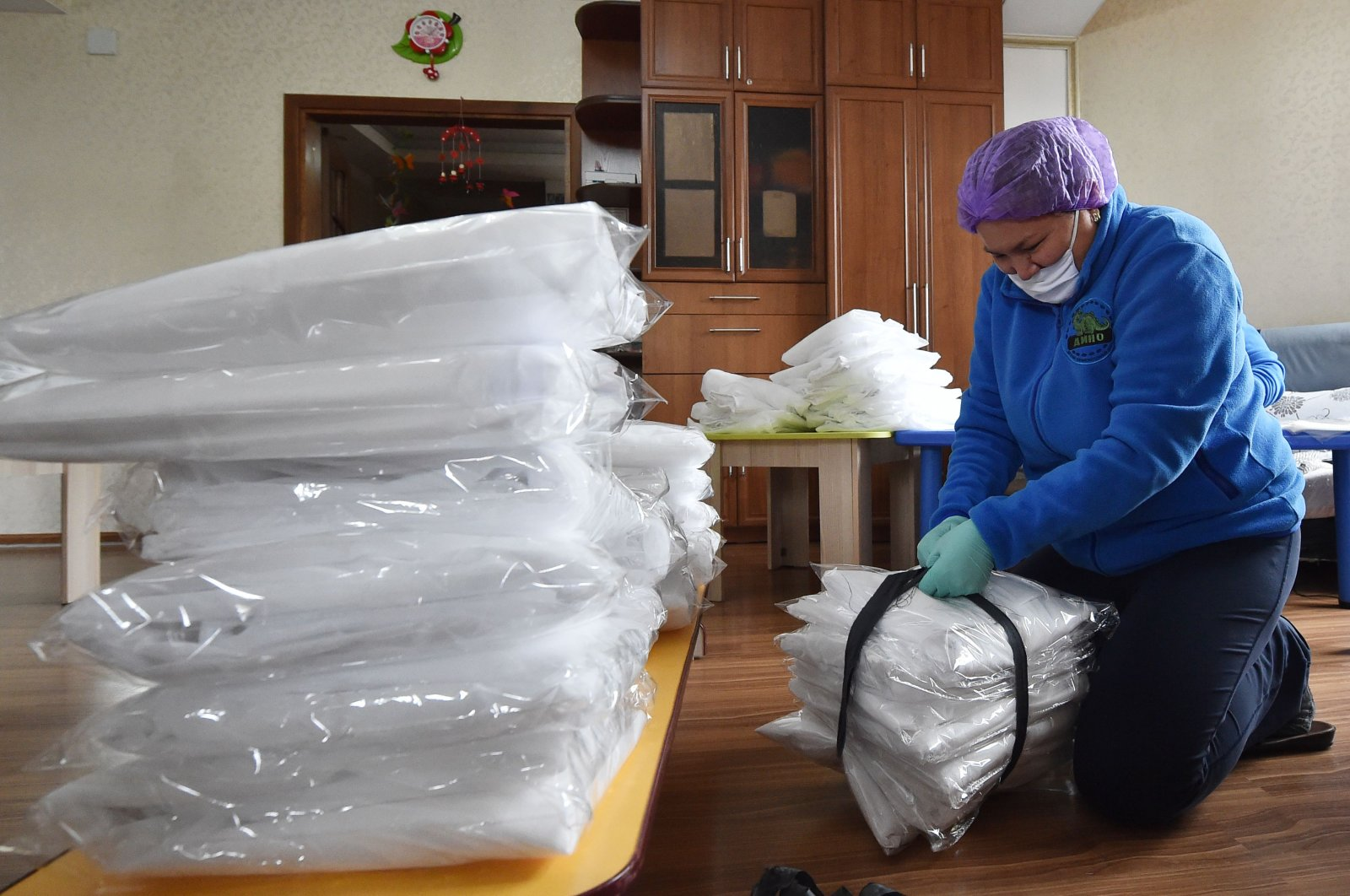 Civil activists wearing face masks and protective gloves pack protective suits before supplying to hospitals in Kyrgyzstan, in Bishkek on April 15, 2020. (AFP Photo)