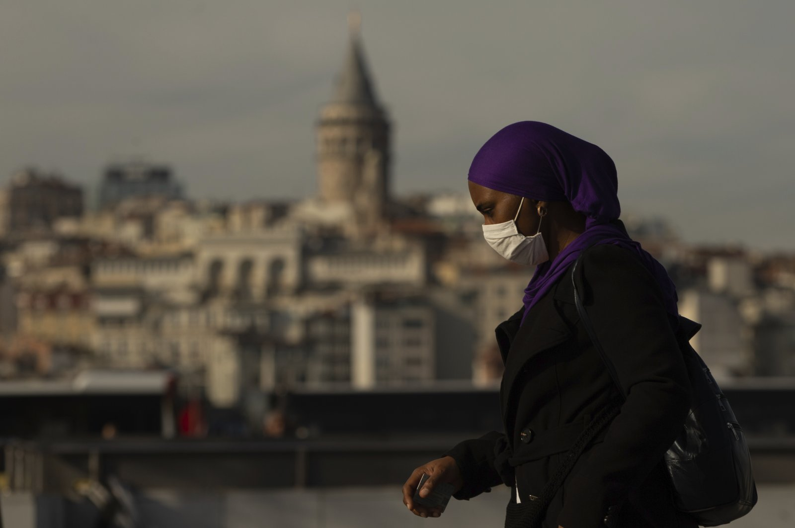 Backdroped by Istanbul's iconic Galata Tower a woman, wearing a mask as a preventive measure against the spread of coronavirus, walks in Istanbul, Friday, April 17, 2020. (AP Photo)