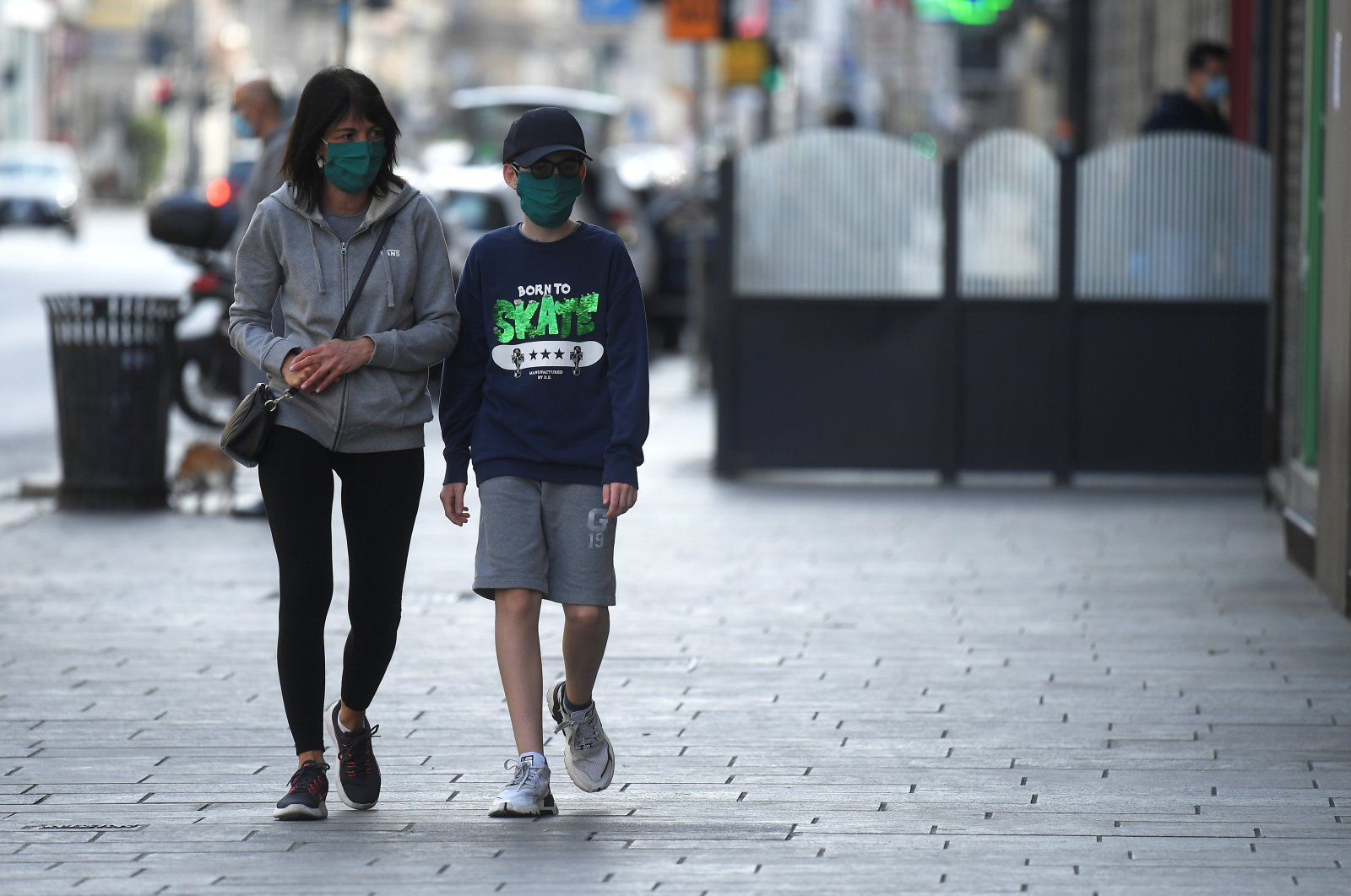 People wearing face masks walk on a street, amid the coronavirus disease (COVID-19) outbreak, in Milan, Italy April 18, 2020. (Reuters Photo)