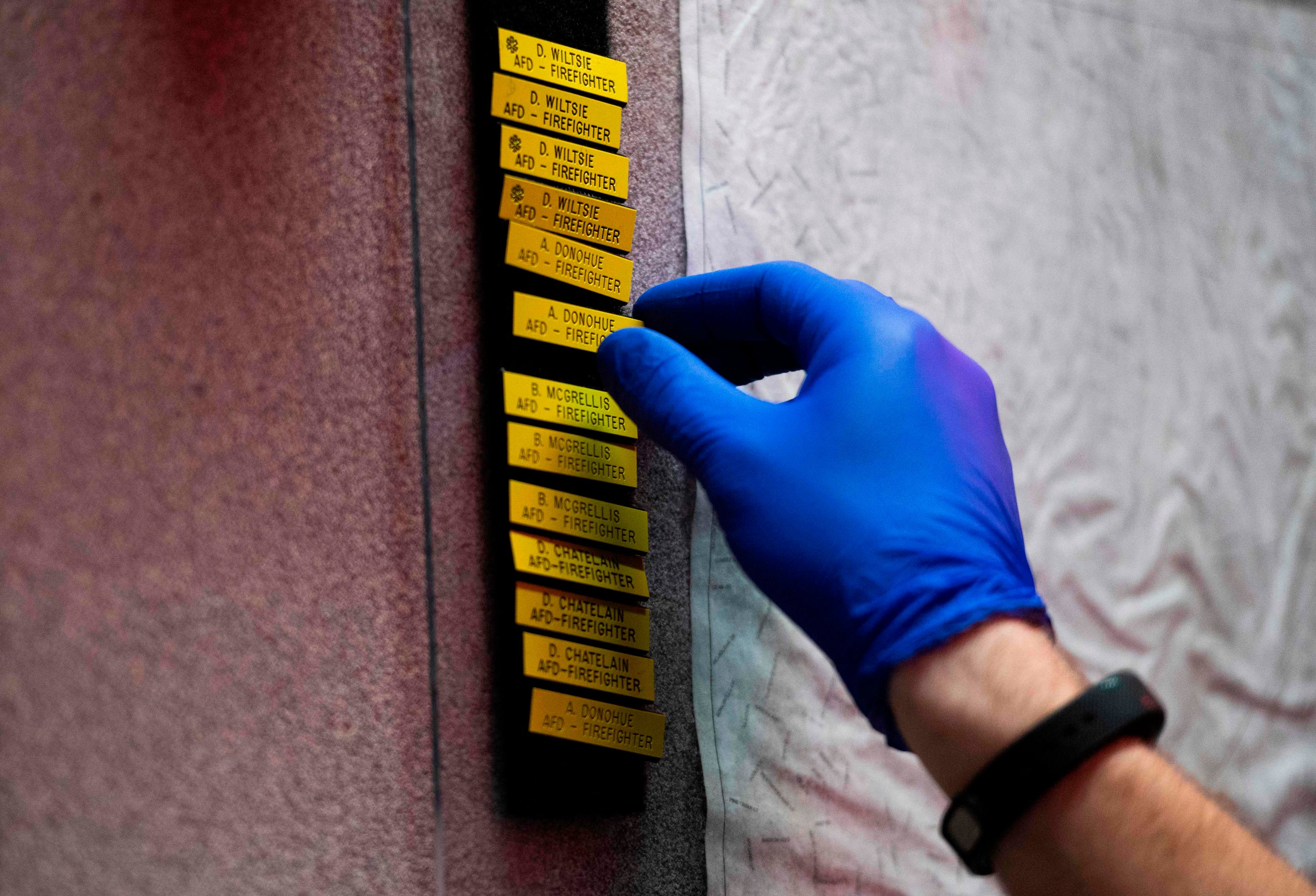 A firefighter wears surgical gloves while taking the names of firefighters off a board at Alexandria Fire Station 204 in Alexandria, Virginia, April 8, 2020. (AFP Photo)