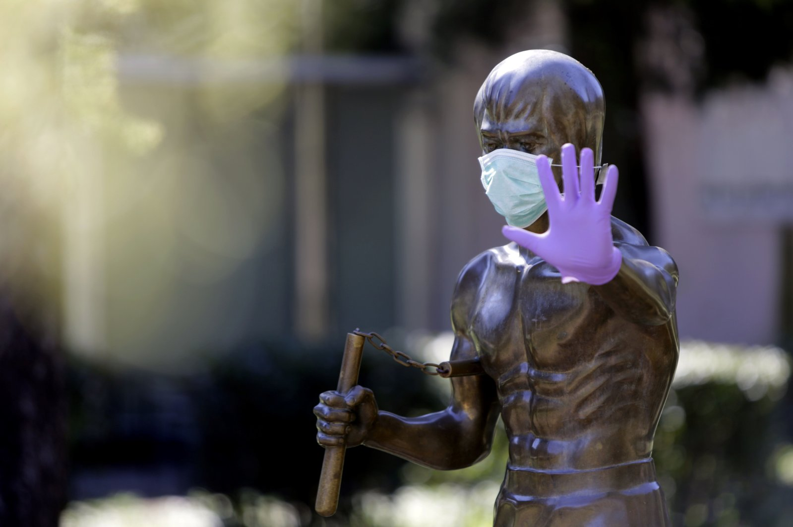 The statue dedicated to martial arts icon and actor Bruce Lee, wearing surgical gloves and a face mask, in the central park of Mostar, Bosnia-Herzegovina, April 2, 2020. (Photo by STR / AFP)