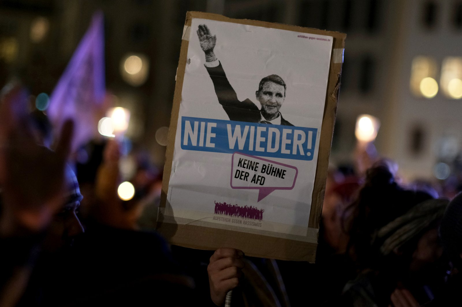 """People attend a demonstration as supporters of the right-wing anti-Islam movement Patriotic Europeans Against the Islamisation of the West (PEGIDA) stage a protest in Dresden, Germany, Feb. 17, 2020. The banner reads: """"Never again. No stage for the AfD."""" (Reuters Photo)"""