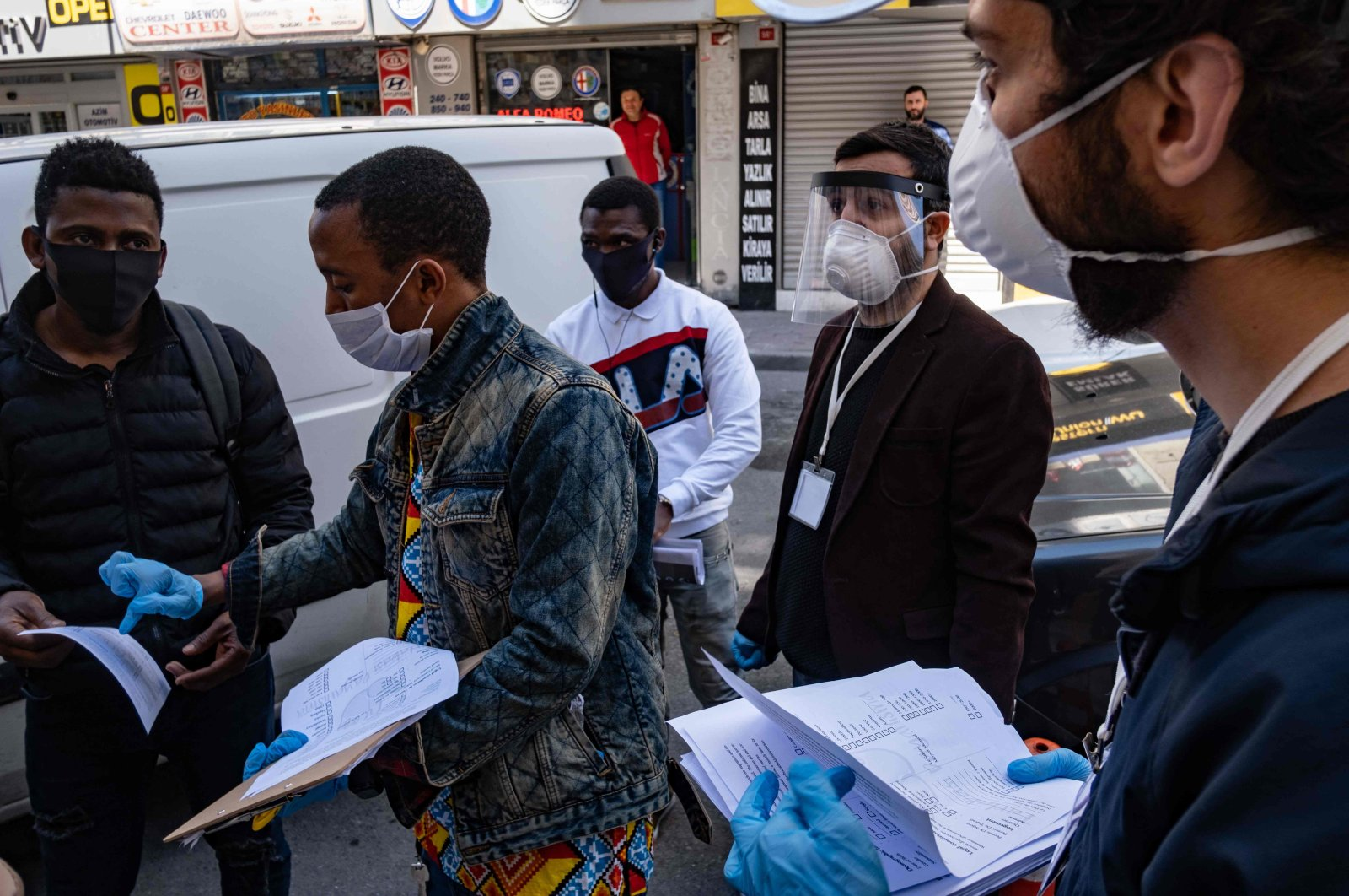 Members of a solidarity network hand out disinfectant, gloves and face masks as well as food cards to African migrants in Istanbul, April 17, 2020. (AFP Photo)