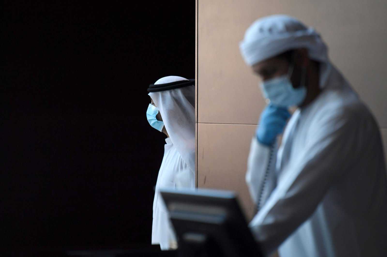Emirati hotel staff wearing protective masks and gloves work at a hotel where families returning to the UAE will stay 14-days in quarantine amid the COVID-19 on April 14, 2020 in Dubai. (AFP Photo)