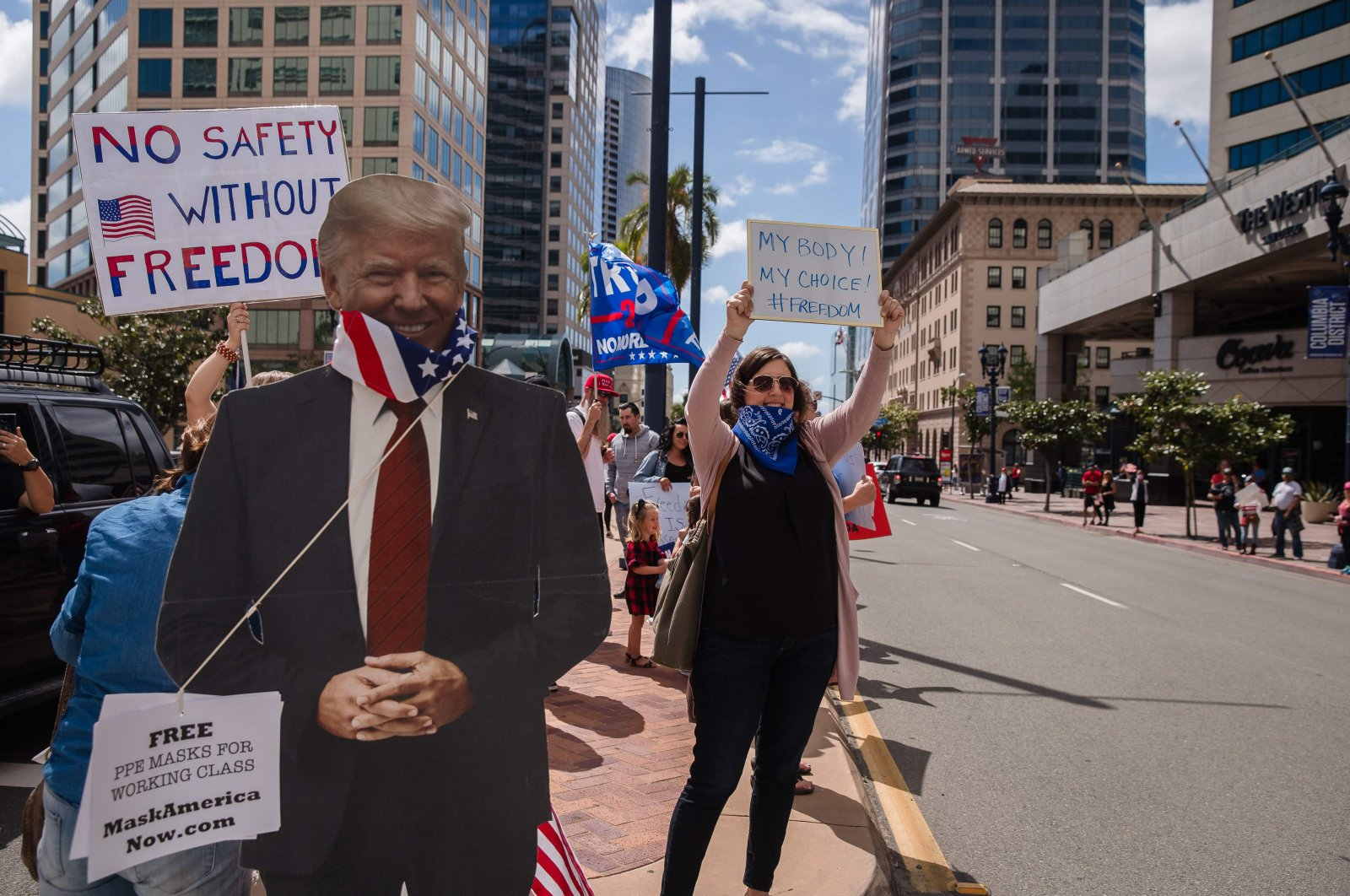 A Trump cutout with a US flag around its neck is seen next to protesters rallying in downtown San Diego against California's stay at home order to prevent the spread of the novel coronavirus, which causes COVID-19, on April 18, 2020. (AFP Photo)