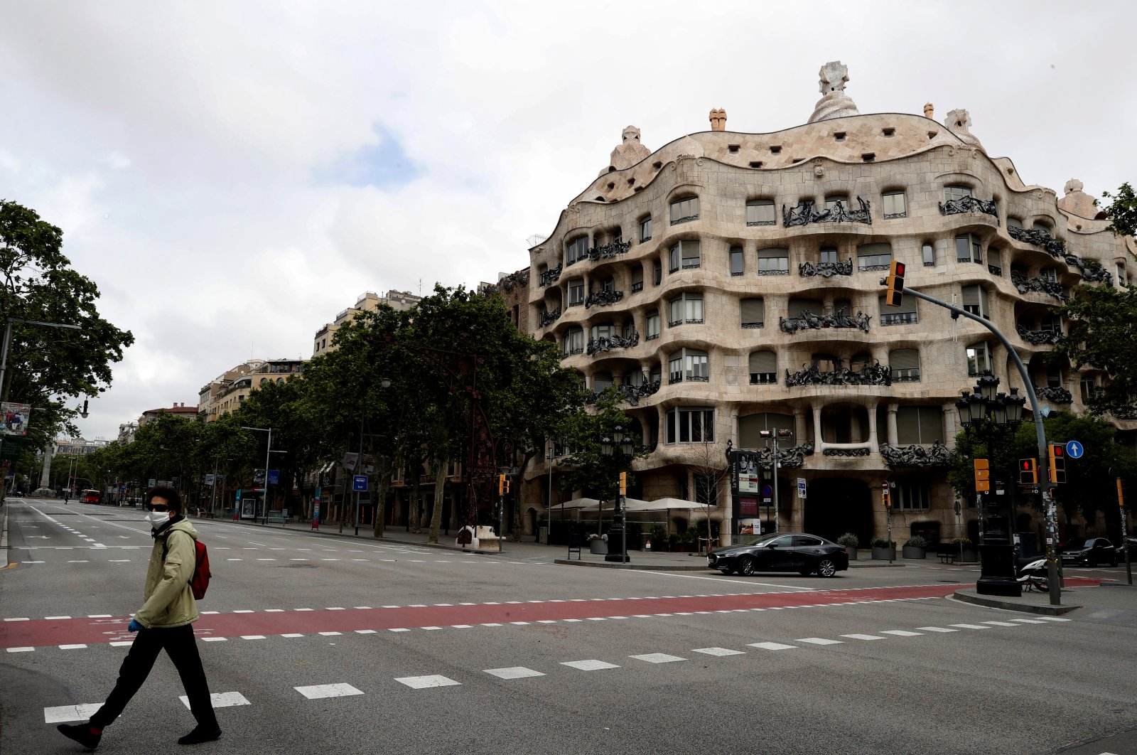 A man promenades with his dog in front of Pedrera's bulding by Guadi at Paseo de Gracia street in an empty Barcelona, Spain,18 April 2020, during the coronavirus crisis. (EPA-EFE/Toni Albir Photo)