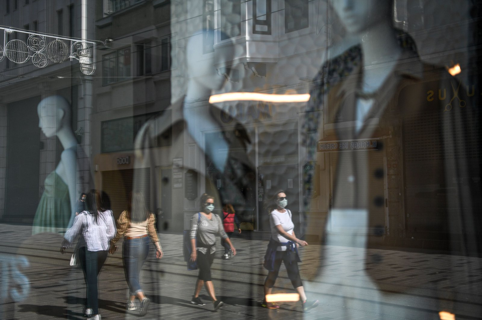 People wearing face masks due to coronavirus are reflected in a window shop of the Istiklal avenue before a weekend lockdown in Istanbul, Turkey, April 14, 2020.  (AFP Photo)