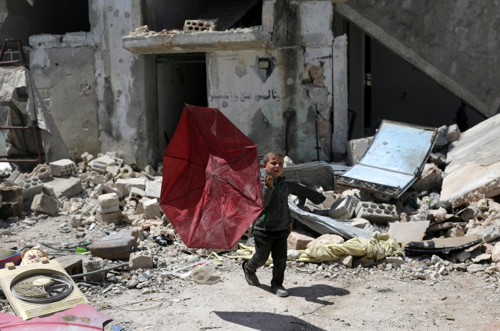 A boy carries a broken umbrella as he walks past a damaged building in the rebel-held town of Nairab, in northwest Syria's Idlib region, Syria, Friday, April 17, 2020. REUTERS