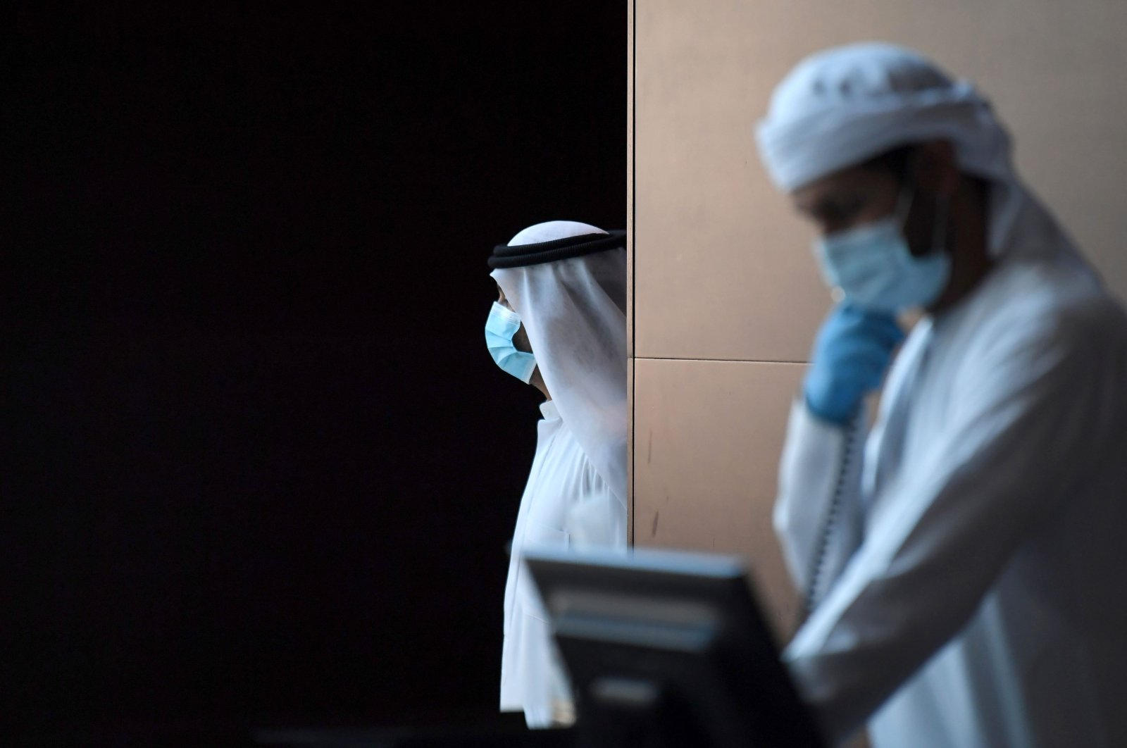Emirati hotel staff wearing protective masks and gloves work at a hotel where families returning to the UAE will stay 14-days in quarantine amid the COVID-19, Dubai, Tuesday, April 14, 2020. (AFP Photo)