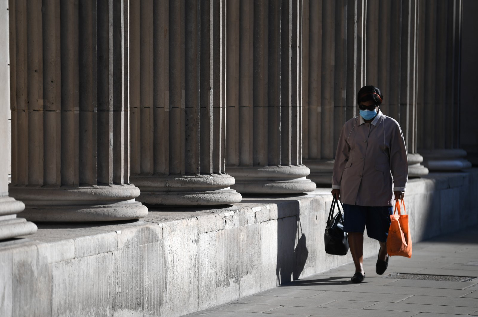 A masked woman passes the Bank of England in The City of London financial district in London, Britain, 15 April 2020. (EPA-EFE/NEIL HALL Photo)