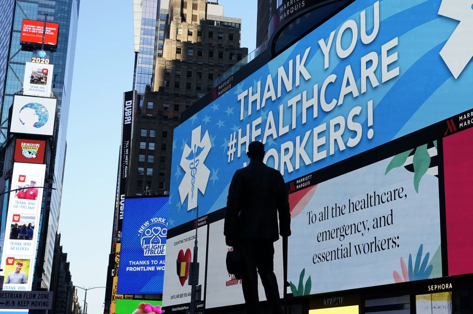 The statue of composer George M. Cohan is seen in Times Square in New York City, while in the background some of the nearly 1,800 digital billboards and screens across all five boroughs are displaying messages of public safety, gratitude, pride and solidarity with essential workers, New York, U.S., April 19, 2020. (AFP Photo)