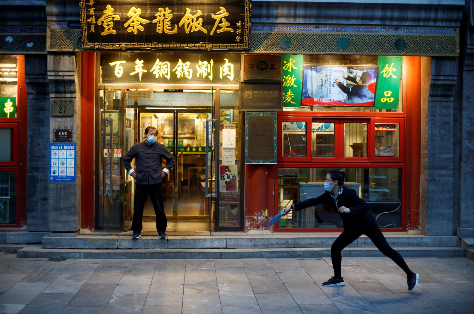 Staff play badminton outside their restaurant in the Qianmen district, one of the top tourist destinations in Beijing, as the coronavirus outbreak continues in China, April 8, 2020. (Reuters Photo)