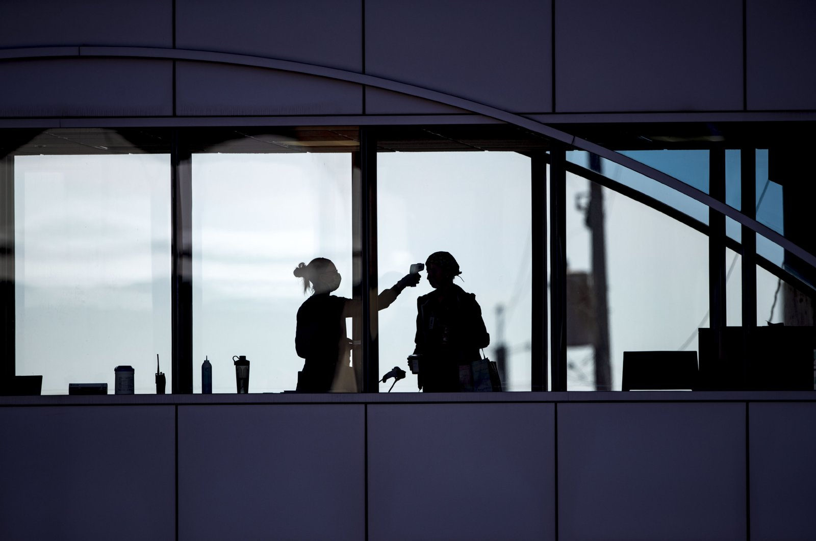 Amid coronavirus concerns, a health care worker takes the temperature of a visitor at Essentia Health who was crossing over a skywalk bridge from the adjoining parking deck in Duluth, Minnesota, April 10, 2020. (AP Photo)