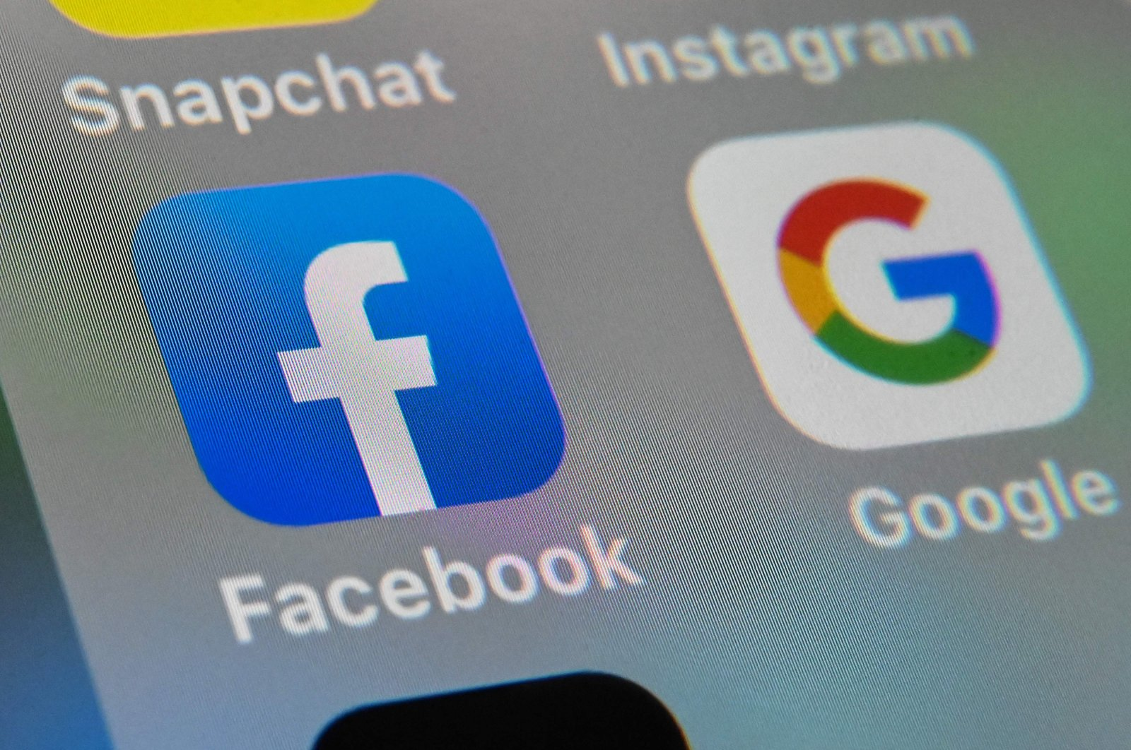 The logos of mobile apps Facebook and Google are displayed on a tablet in Lille, France, Oct. 1, 2019. (AFP Photo)