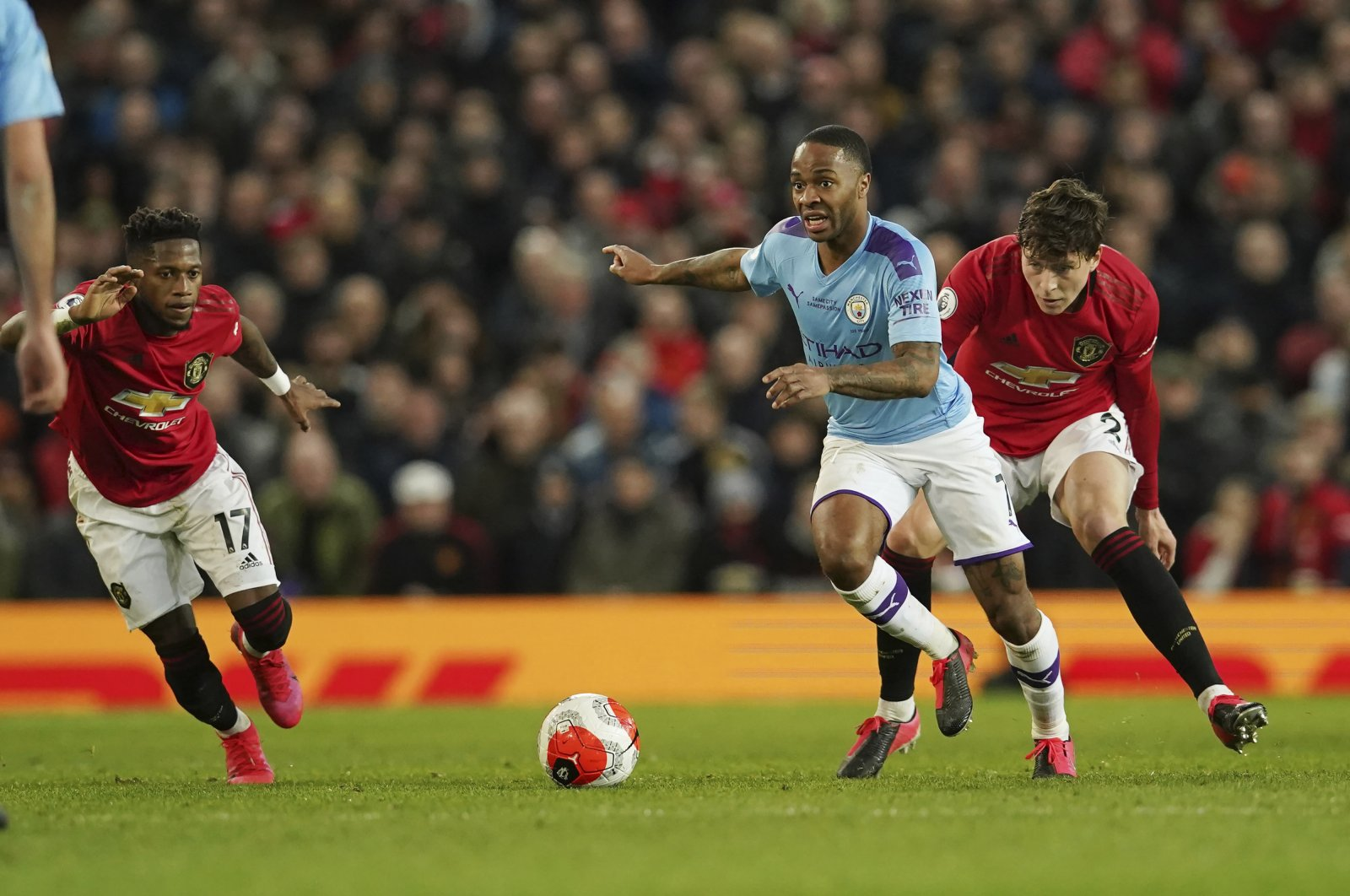 Manchester City's Raheem Sterling (C) and Manchester United's Victor Lindelof (R) compete for the ball during a Premier League match in Manchester, England, March 8, 2020. (AP Photo)