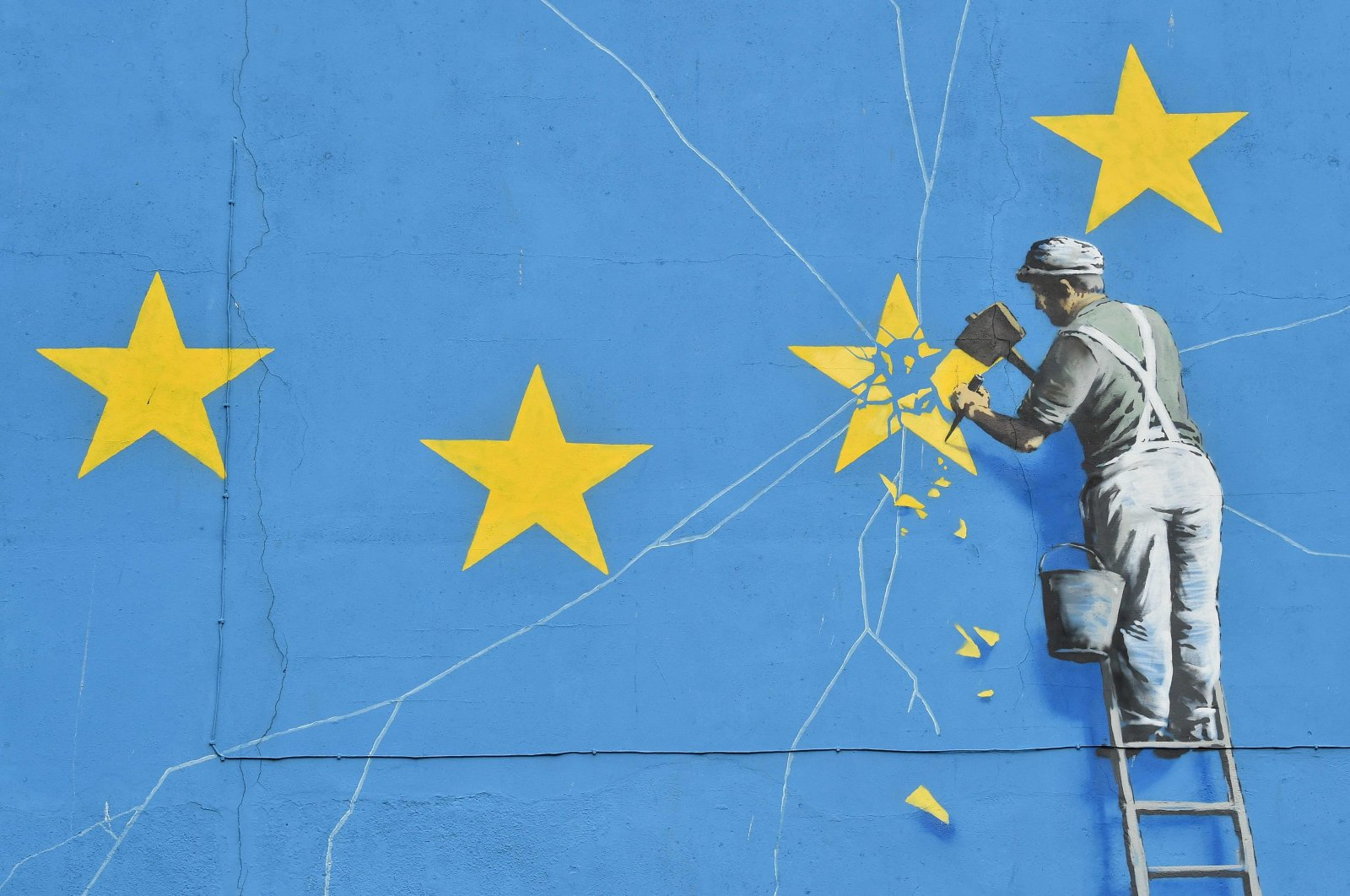 This file photo taken on January 7, 2019 shows a mural by British artist Banksy, depicting a workman chipping away at one of the stars on a European Union (EU) themed flag,in Dover, south east England. - Britain leaves the European Union on January 31, ending more than four decades of economic, political and legal integration with its closest neighbours. (Photo by Glyn KIRK / AFP)