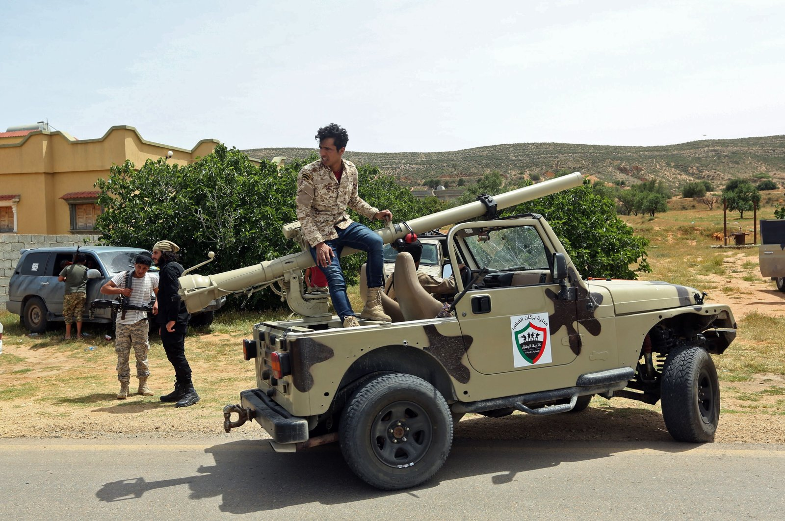 Fighters with Libya's UN-recognised Government of National Accord (GNA) gather at a position near the town of Garabulli, some 70 kms east of the capital Tripoli on April 19, 2020. (AFP)