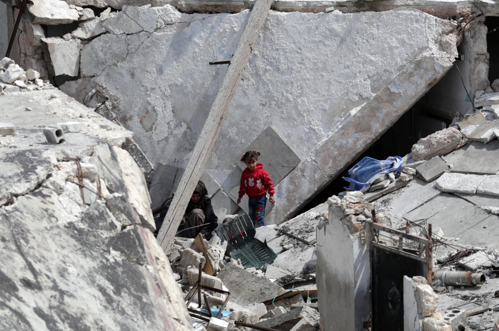 A girl stands near a woman on the rubble of a damaged building in the opposition-held town of Nairab, in northwest Syria's Idlib region, Syria April 17, 2020. REUTERS