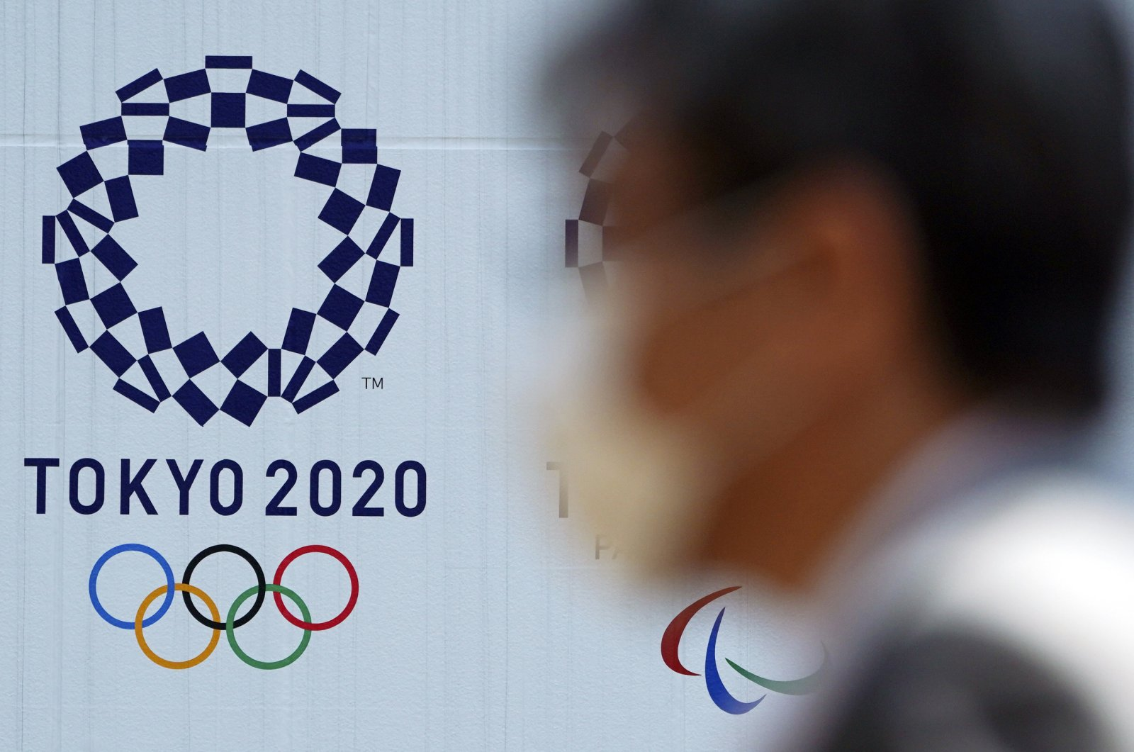 A man wearing a face mask walks near the logo of the Tokyo 2020 Olympics, in Tokyo, April 2, 2020. (AP Photo)