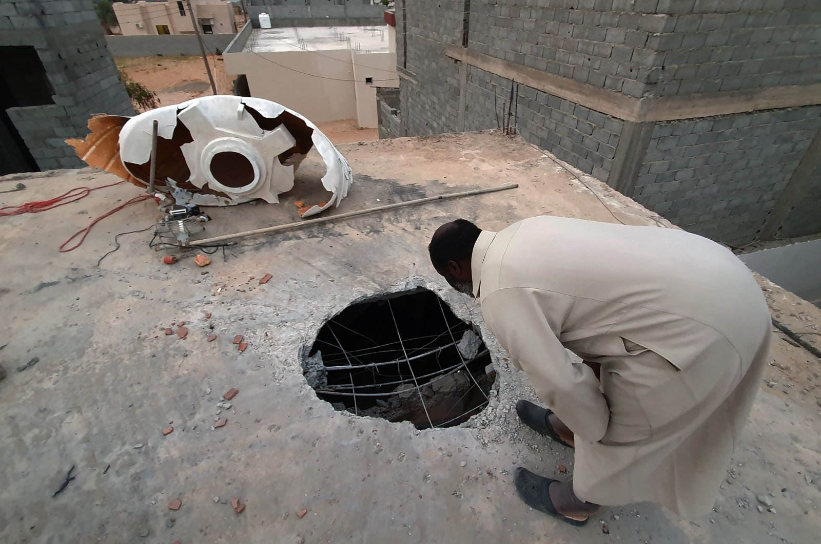 A Libyan checks the site of shelling on the residential area of Arada in the capital Tripoli on April 14, 2020. (AFP)