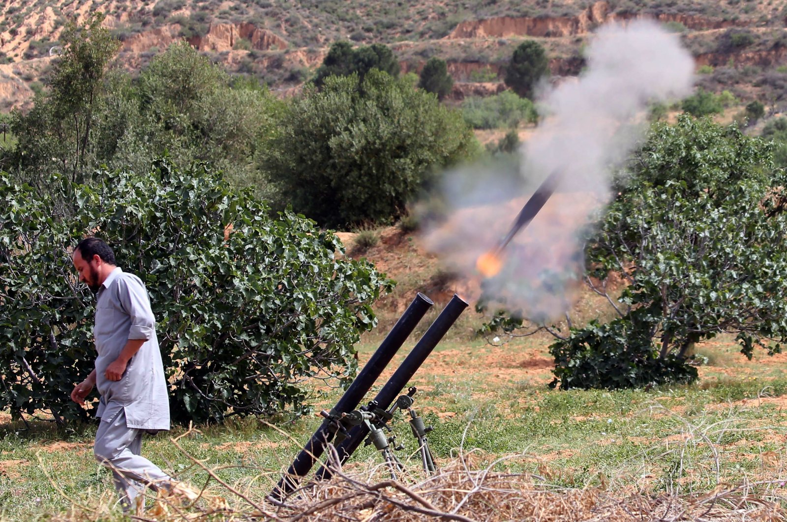 A fighter with Libya's UN-recognised Government of National Accord (GNA) fires rockets from a position near the town of Garabulli toward the city of Tarhuna, on April 19, 2020. (AFP)