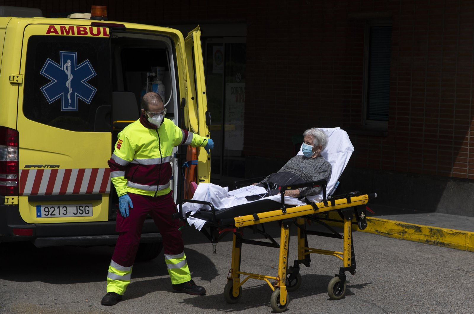An emergency worker wearing a face mask transports an elderly patient to an ambulance at the Severo Ochoa Hospital in Leganes, Spain, April 18, 2020. (AP Photo)