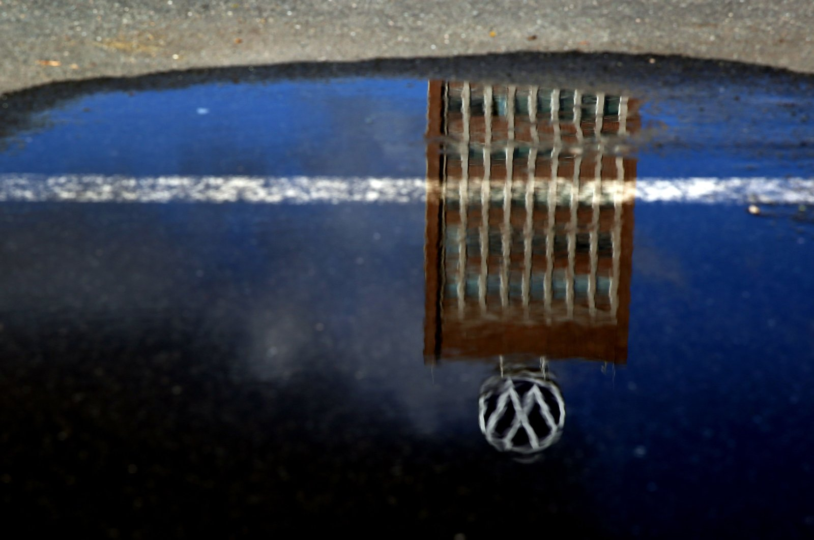The headquarters of German carmaker Volkswagen (VW) reflects in a puddle in Wolfsburg, Germany, Feb. 28, 2020. (AFP Photo)