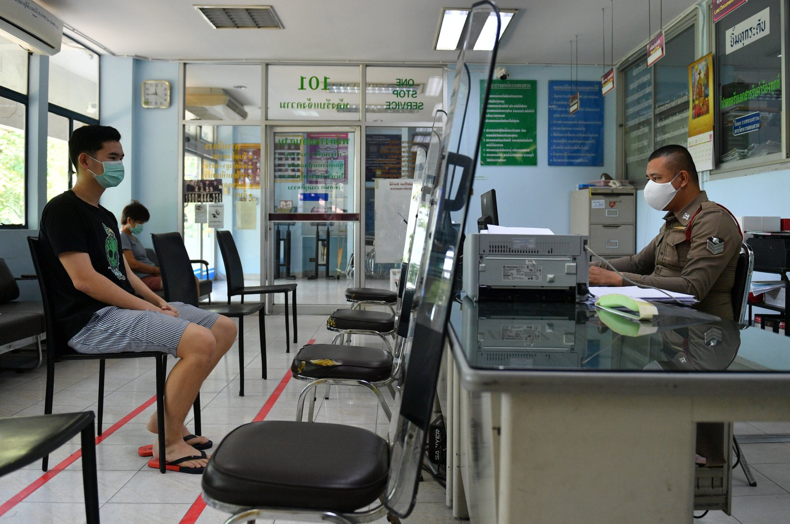 Citizens and police officers wearing protective face masks due to the coronavirus disease (COVID-19) outbreak keep social distance at a police station in Bangkok, Thailand, March 28, 2020. (Reuters Photo)