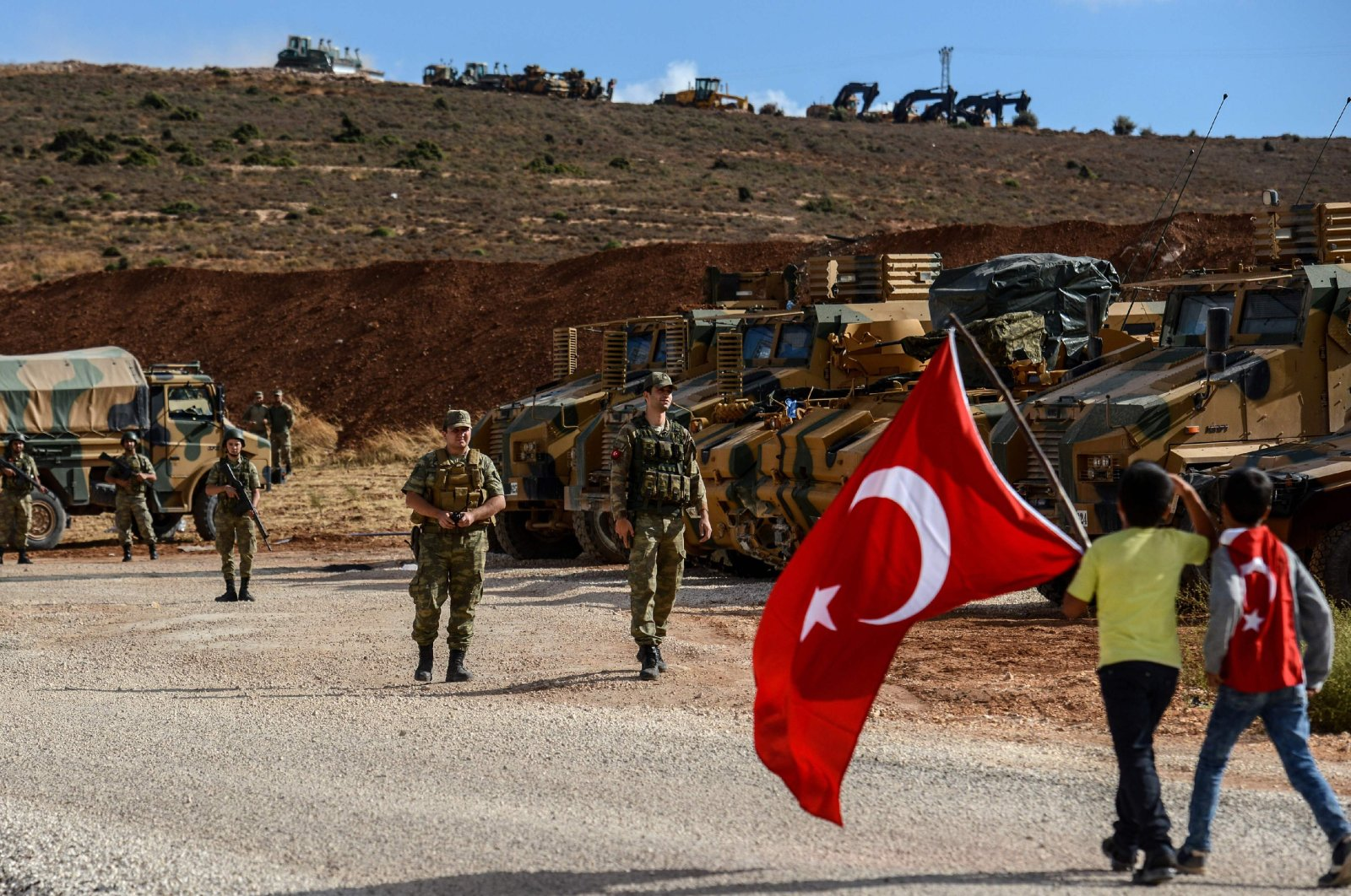 Turkish soldiers stand near armored vehicles as two young boys holding Turkish national flags arrive during a demonstration in support of the Turkish army's Idlib operation near the Turkey-Syria border near Reyhanli, Hatay, Oct. 10, 2017. (AFP photo)