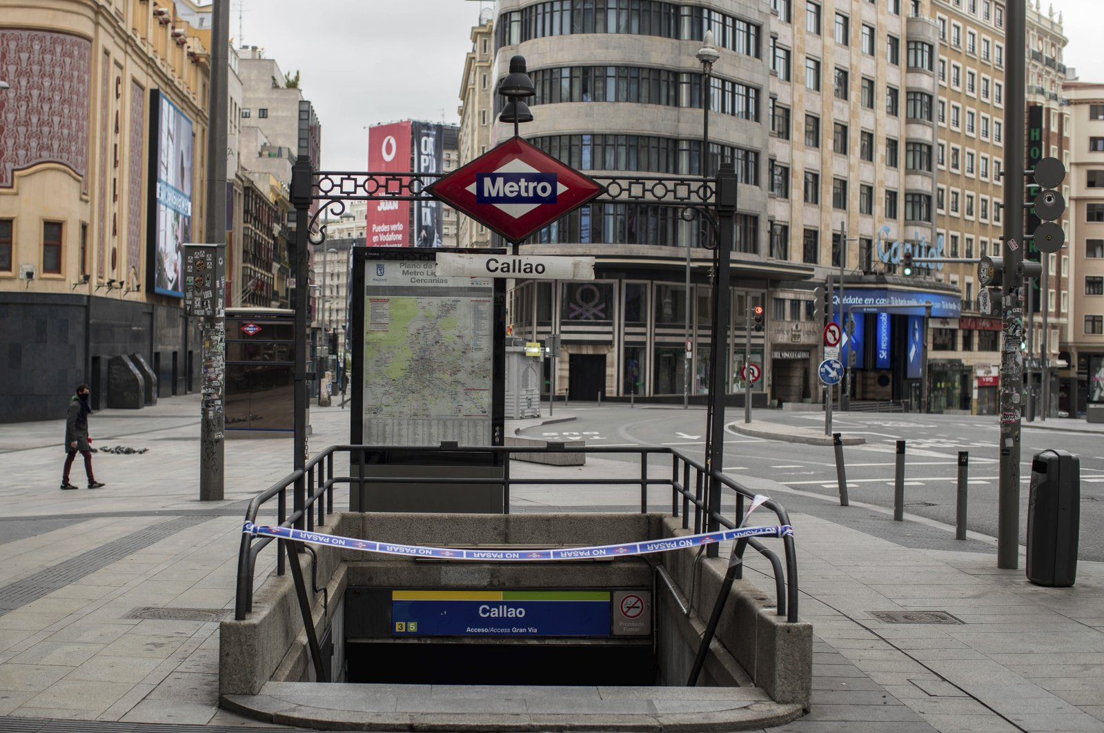 A man walks past a closed subway station during the lockdown to combat the spread of the coronavirus in downtown Madrid, Spain, April 14, 2020. (AP Photo)